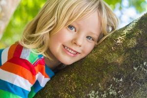 Cute happy child relaxing outdoors in tree